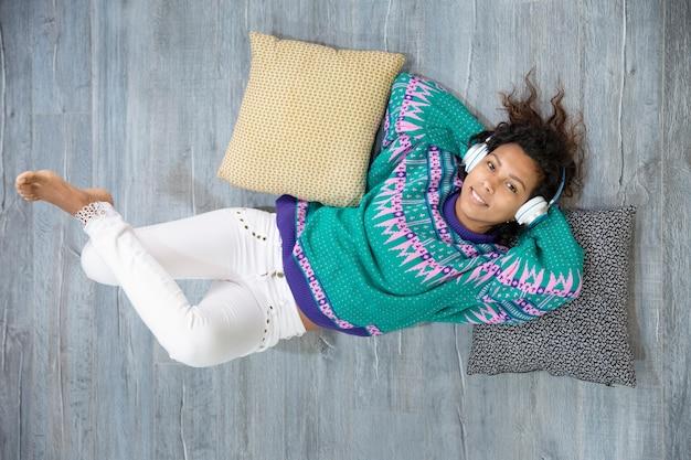 彼女の家の床に横たわって音楽を聴いて笑顔でリラックスしたラテンの女の子の上面図。テキスト用のスペース。 Premium写真