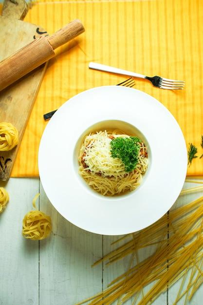黄色の白いボウルにパルメザンチーズのボロネーゼのトップビュー 無料写真