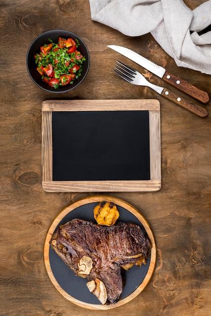 Вид сверху стейк на тарелку с салатом и доске Бесплатные Фотографии