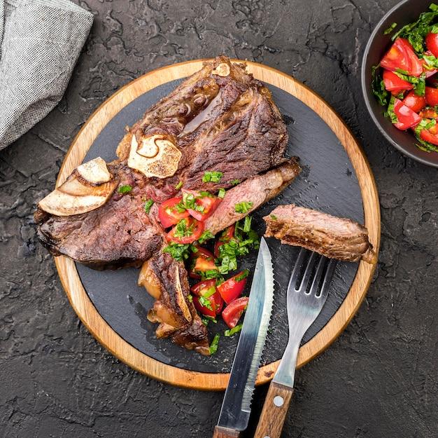 Вид сверху стейк со столовыми приборами и салатом Premium Фотографии