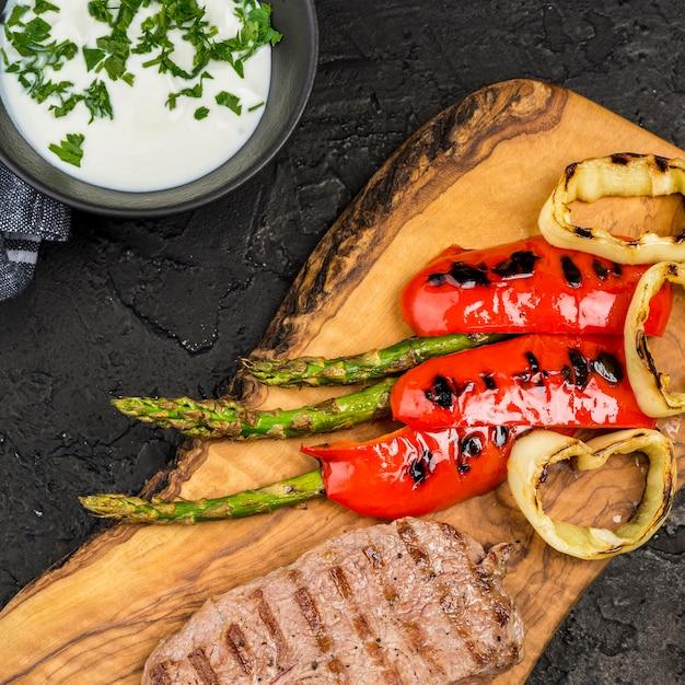 Вид сверху стейк с соусом и овощами Бесплатные Фотографии