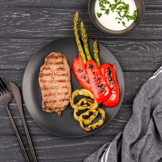 Вид сверху стейк с овощами и соусом Premium Фотографии