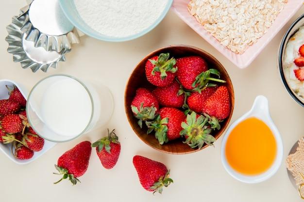 Вид сверху клубники в миску и стакан молока и топленого масла с мукой и овсом на белой поверхности Бесплатные Фотографии