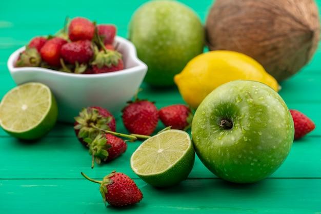Вид сверху клубники на миске со свежими фруктами, такими как яблоки, лимонный кокос, изолированные на зеленом фоне Бесплатные Фотографии