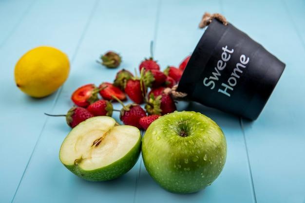 青色の背景にレモンと緑のリンゴとバスケットから落ちるイチゴのトップビュー 無料写真