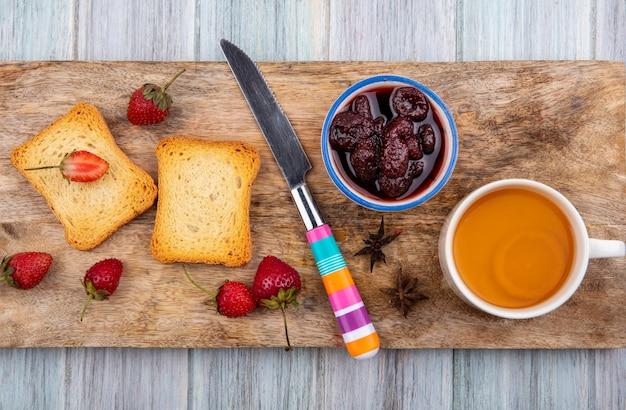 灰色の木製の背景に新鮮なイチゴとパンのトーストスライスとナイフで木製キッチンボード上のボウルにいちごジャムのトップビュー 無料写真