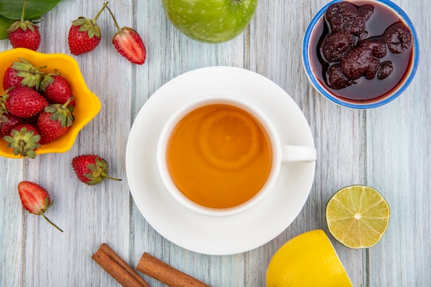 Вид сверху клубничного джема на миске с чашкой чая со свежей клубникой на желтой миске на сером деревянном фоне Бесплатные Фотографии