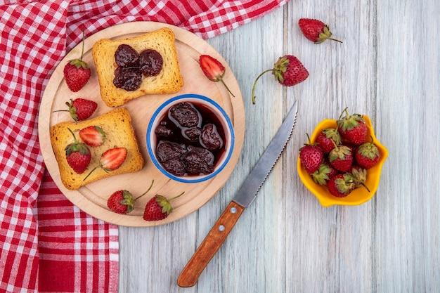 灰色の木製の背景に黄色のボウルにナイフと新鮮なイチゴとナイフで木製キッチンボードに新鮮なイチゴとボウルにいちごジャムのトップビュー 無料写真