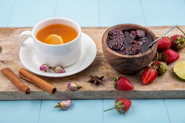 Вид сверху клубничного джема на деревянной миске на деревянной кухонной доске с чашкой чая с корицей на синем фоне Бесплатные Фотографии