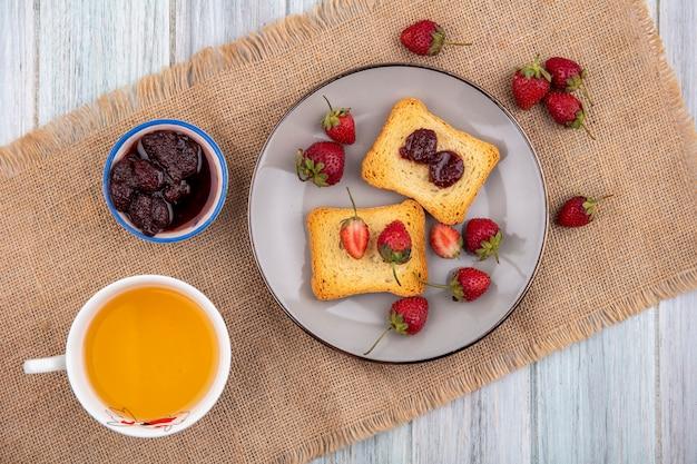 灰色の木製の背景にいちごジャムとお茶のカップと袋布のプレートにイチゴのトップビュー 無料写真