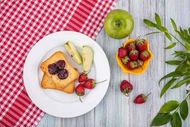 木製の背景が灰色の葉と黄色のボウルに新鮮なイチゴと赤いチェックのテーブルクロスに緑のリンゴと白い皿にイチゴの平面図 無料写真
