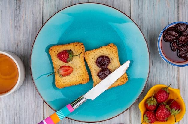 灰色の木製の背景に新鮮なイチゴをボウルにイチゴジャムとナイフで青い皿にパンにイチゴのトップビュー 無料写真