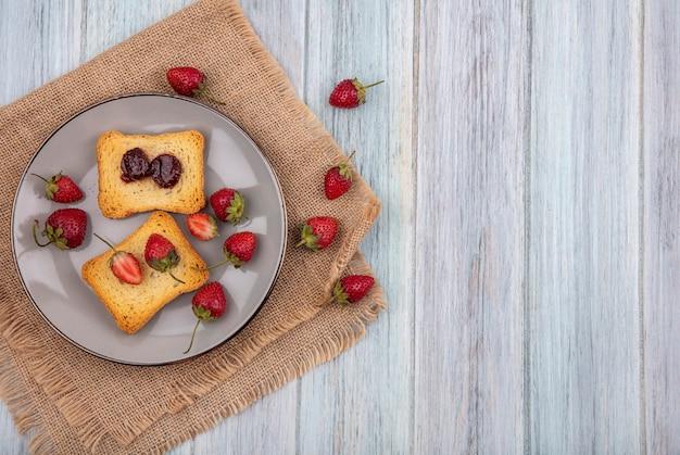 コピースペースを持つ灰色の木製の背景に袋布に新鮮なイチゴとプレートのトーストしたパンにイチゴのトップビュー 無料写真