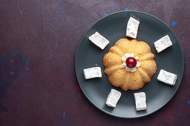 Вид сверху сахарной пудры, вкусной нуги с тортом внутри тарелки на темной поверхности Бесплатные Фотографии