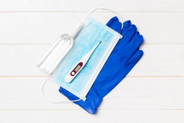 手術用手袋、手の消毒剤と温度計のボトルのトップビュー Premium写真