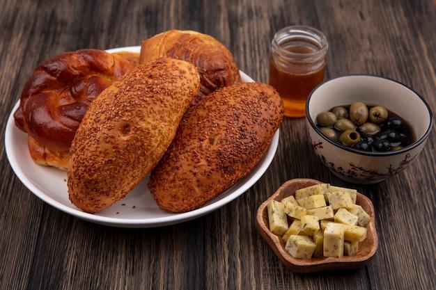 木製の背景にオリーブとチーズの刻んだスライスとプレート上のおいしいパンの上面図 無料写真