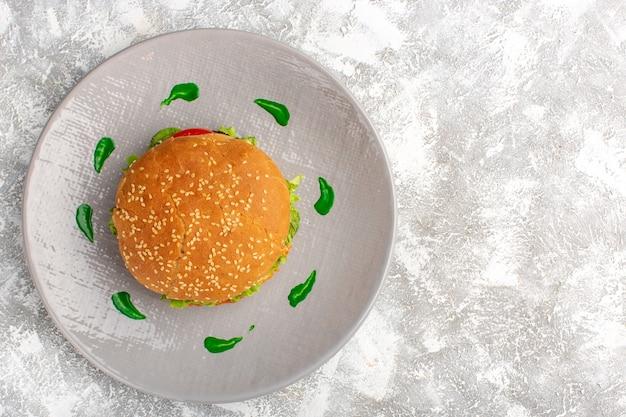白い表面のプレートの中にグリーンサラダと野菜とおいしいチキンサンドイッチの上面図 無料写真
