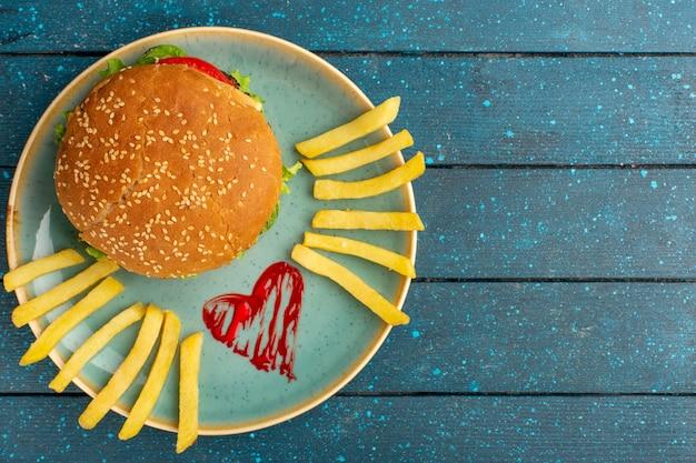 Вид сверху вкусного куриного сэндвича с зеленым салатом и овощами внутри тарелки с картофелем фри на деревянной синей поверхности Бесплатные Фотографии