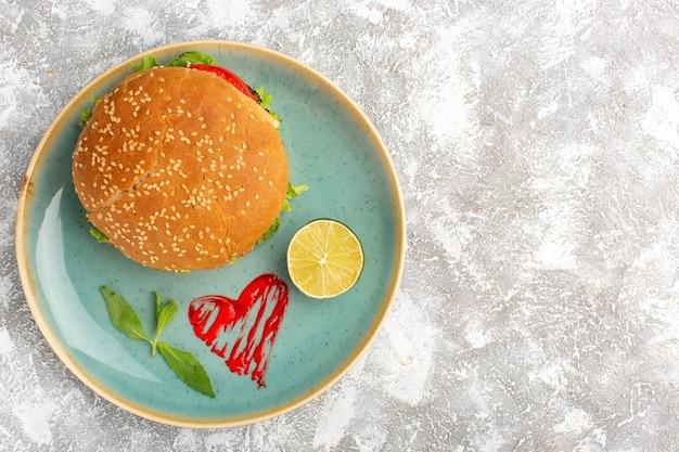 Вид сверху вкусного куриного сэндвича с зеленым салатом и овощами внутри тарелки с лимоном на светлой поверхности Бесплатные Фотографии