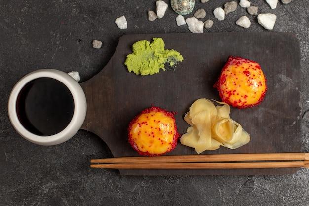 Вид сверху вкусных суши-рулетов с рыбой и рисом вместе с соусом на серой стене Бесплатные Фотографии