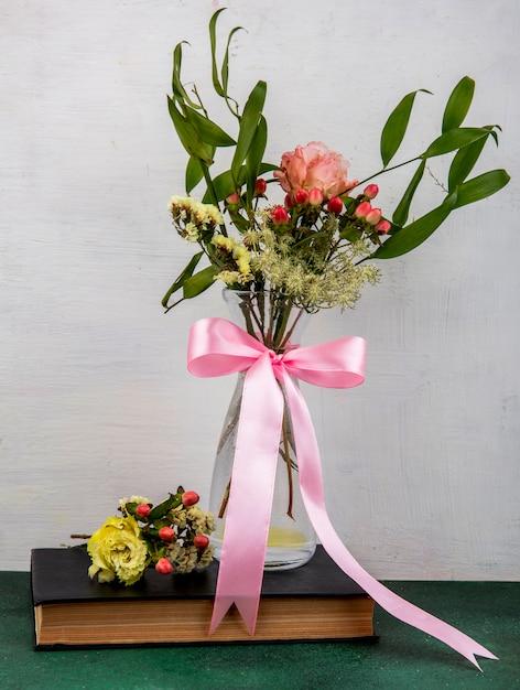 Вид сверху нежных и прекрасных цветов с листьями на стеклянной вазе на белой поверхности Бесплатные Фотографии