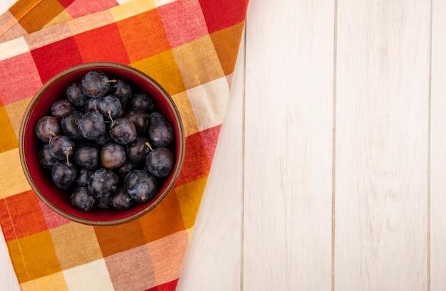 Вид сверху небольших кислых сине-черных фруктовых тернов на миске на клетчатой скатерти на белом деревянном фоне с копией пространства Бесплатные Фотографии