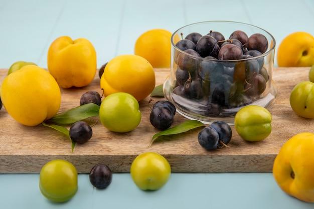 Вид сверху небольших кислых сине-черных ягод на стеклянной миске на деревянной кухонной доске с зелеными алычами с желтыми персиками на синем фоне Бесплатные Фотографии