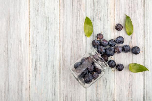 コピースペースを持つ灰色の木製の背景に葉が付いているガラスの瓶から落ちる小さな酸っぱい青黒のスローのトップビュー 無料写真