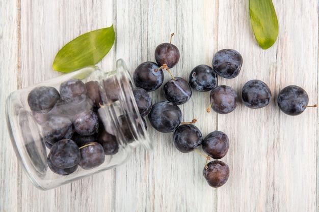灰色の木製の背景に葉が付いているガラス瓶から落ちる小さな酸っぱい青黒のスローのトップビュー 無料写真
