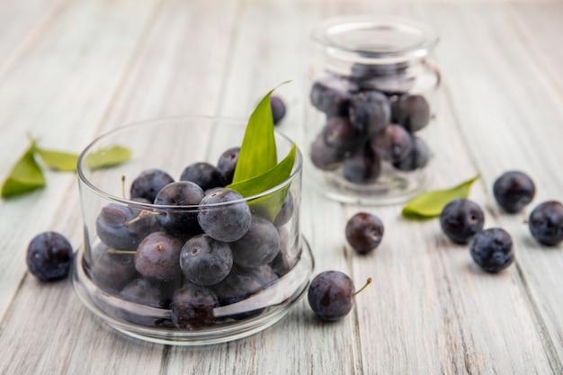 灰色の木製の背景の葉とガラスの瓶にスローのガラスのボウルに小さな酸っぱい青黒スローのトップビュー 無料写真