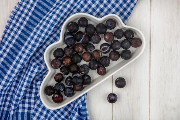 Вид сверху небольших кислых сине-черных ягод на белой миске на синей клетчатой скатерти на сером деревянном фоне Бесплатные Фотографии