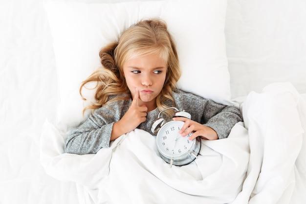 Взгляд сверху заботливой маленькой девочки лежа в кровати с будильником, смотря в сторону Бесплатные Фотографии