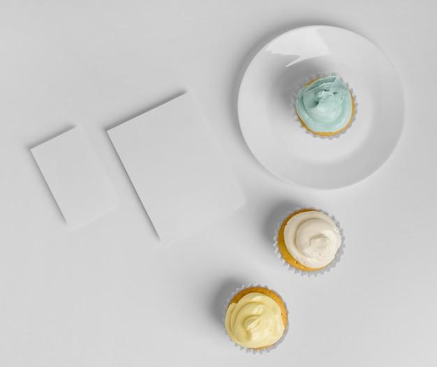 空白のカードとプレート上の3つのカップケーキの上面図 無料写真
