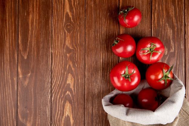 右側の袋からこぼれるトマトとコピースペースを持つ木材のトップビュー 無料写真