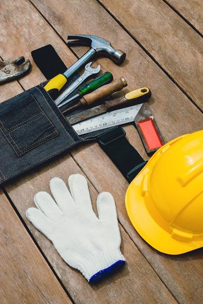 ツールベルトバッグと古い楽器コンストラクターまたは素朴なグランジ木製の背景に家を建てると修理のための改修の平面図 Premium写真
