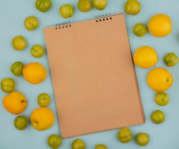 Вид сверху на свежие вкусные желтые персики с зелеными алычами, изолированные на синем фоне с копией пространства Бесплатные Фотографии
