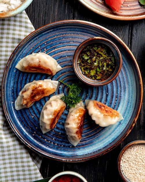 素朴なテーブルの皿に醤油を添えて肉と野菜の伝統的なアジア餃子のトップビュー 無料写真