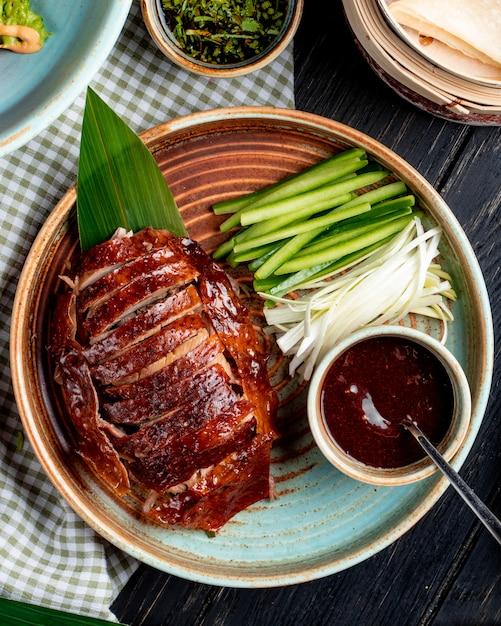 皿にキュウリとソースの伝統的なアジア料理北京ダックのトップビュー 無料写真