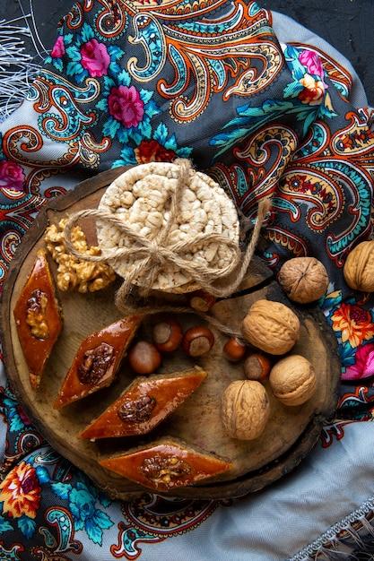 Вид сверху традиционной азербайджанской пахлавы с цельными орехами и рисовым хлебом на платке с кисточкой Бесплатные Фотографии
