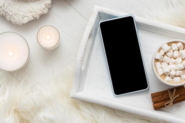 スマートフォンとマシュマロとホットココアのカップとトレイの上面図 Premium写真