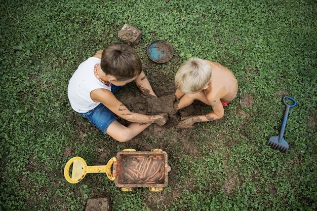 泥で遊んで草の上に座っている2人の兄弟の平面図 Premium写真