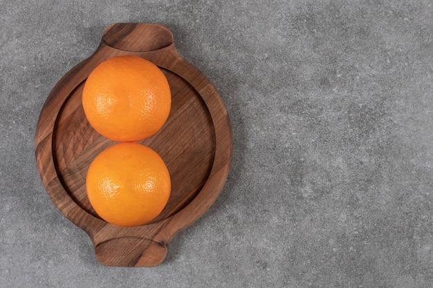 灰色のテーブルの上の木製トレイに2つの熟したオレンジの上面図。 無料写真