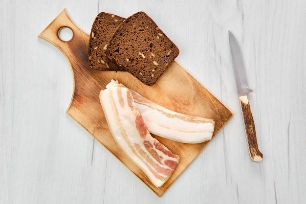 Вид сверху двух кусочков бекона и черного хлеба на деревянной разделочной доске Premium Фотографии