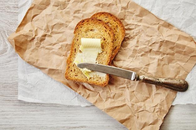 그것에 빈티지 칼으로 아침에 버터 토스트로 호밀 건조 빵 두 조각의 상위 뷰. 공예 종이에있는 모든 것. 무료 사진