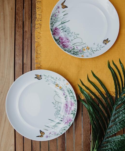 Вид сверху двух столовых пустых тарелок с цветочным узором на желтой салфетке на деревянной стене Бесплатные Фотографии