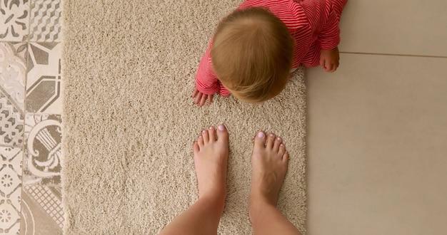 Вид сверху неузнаваемого ребенка в красных ползунках, сидящих на мягком ковре на полу рядом с обрезанными голыми ногами матери Premium Фотографии