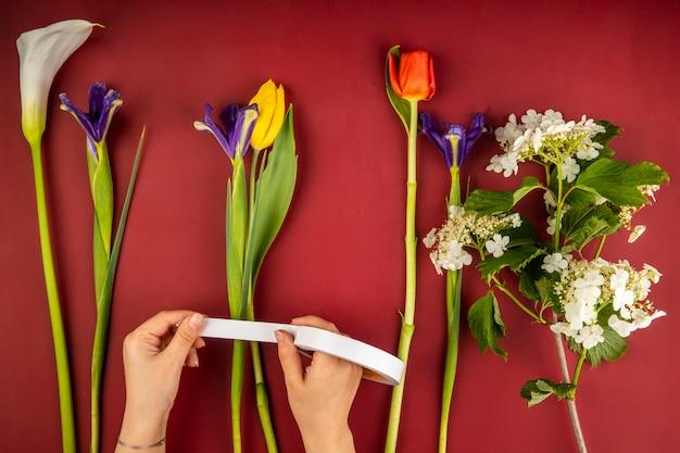 赤と黄色の色のチューリップ、オランダカイウユリ、濃い紫色のアイリスの花、赤いテーブルに咲くガマズミ属の木の花束のさまざまな花のトップビュー 無料写真