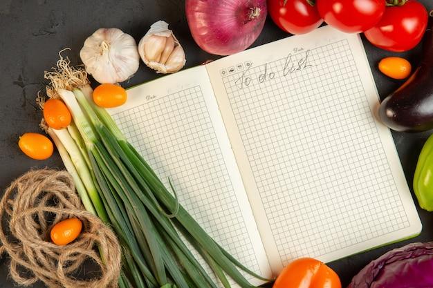 Взгляд сверху различных томатов свежих овощей зеленого лука и чеснока с тетрадью в середине на темноте Бесплатные Фотографии