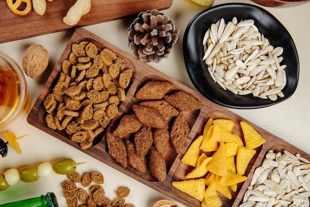 白の様々な塩味のビールスナックパンクラッカーコーンコーンヒマワリの種のナッツとオリーブのピクルスの平面図 無料写真
