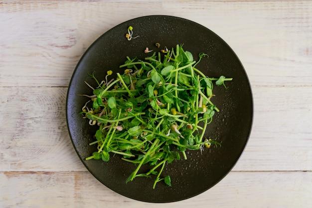 Вид сверху веганский здоровый салат из гороха ростки зелени и проросшие бобы на деревянной стене Premium Фотографии